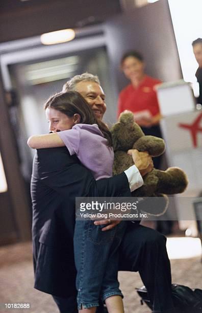 BUSINESSMAN GREETING DAUGHTER AT GATE