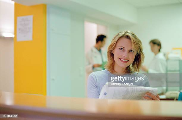WOMAN HOLDING DOCUMENTS IN HOSPITAL