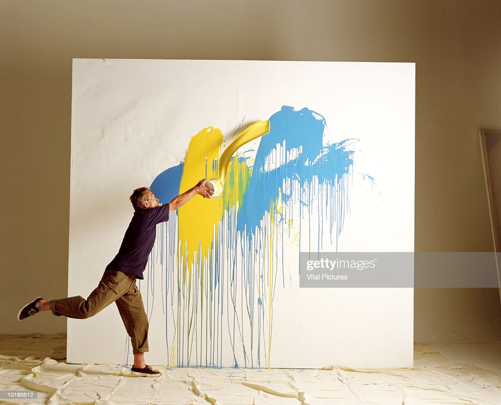 ARTIST THROWING PAINT AT CANVAS : Stock Photo