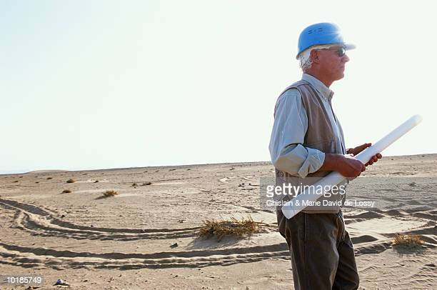 MAN WITH HARD HAT AND BLUEPRINTS IN DESERT