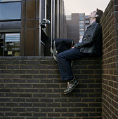 UK, LONDON, YOUNG MAN WEARING HEADPHONES RELAXING ON WALL