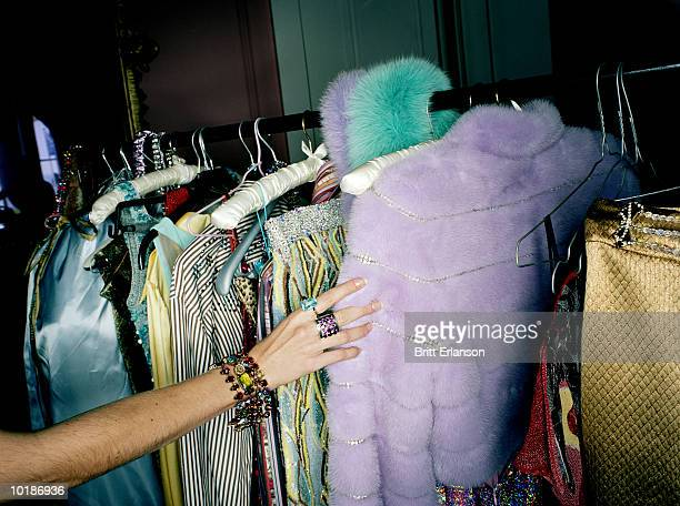 WOMAN SELECTING CLOTHES FROM RAIL, CLOSE-UP
