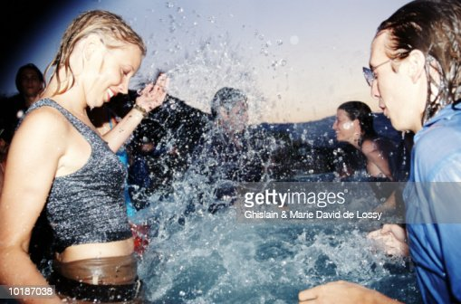YOUNG PEOPLE SPLASHING IN POOL, FULLY CLOTHED : Photo