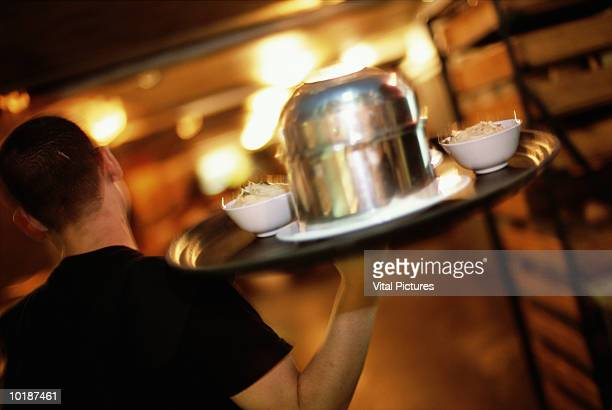 WAITER CARRYING TRAY OF FOOD, REAR VIEW