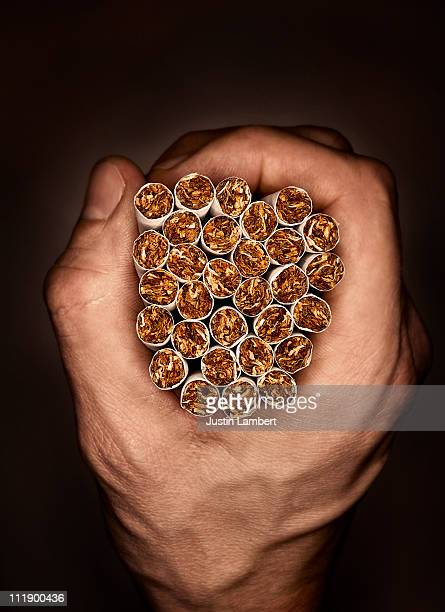 MAN HOLDING BUNCH OF CIGARETTES TO SHOW TOBACCO