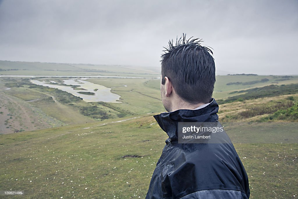 MAN LOOKS AT VIEW ON GREY RAINY DAY : Stock Photo