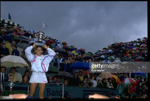 MONICA SELES OF YUGOSLAVIA SHIELDS HERSELF FROM THE RAIN WITH THE TROPHY AFTER DEFEATING STEFFI GRAF OF GERMANY IN THE FINAL OF THE 1990 FRENCH OPEN...
