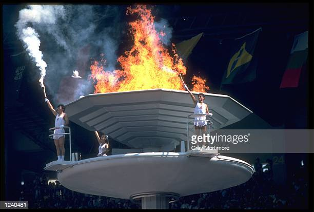 TORCH BEARERS TURN TO SALUTE THE CROWD AFTER LIGHTING THE OLYMPIC FLAME DURING THE OPENING CEREMONY OF THE 1988 SEOUL OLYMPICS