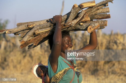 African Woman Carrying Firewood On Head And Baby On Back