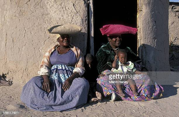 HERERO WOMEN WEARING VICTORIAN-STYLE CLOTHES, MODELLED ON EARLY MISSIONARY S WIVES. ONE WOMAN HOLDING INFANT. SOUTHERN AFRICA