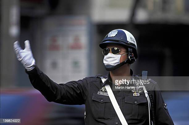POLICEMAN DIRECTING STREET TRAFFIC, WEARING MASK AND SUNGLASSES DUE TO AIR POLLUTION, BANGKOK, THAILAND