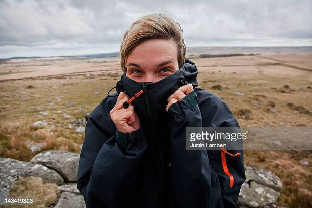 GIRL BRACES HERSELF AGAINST THE WIND ON DARTMOOR