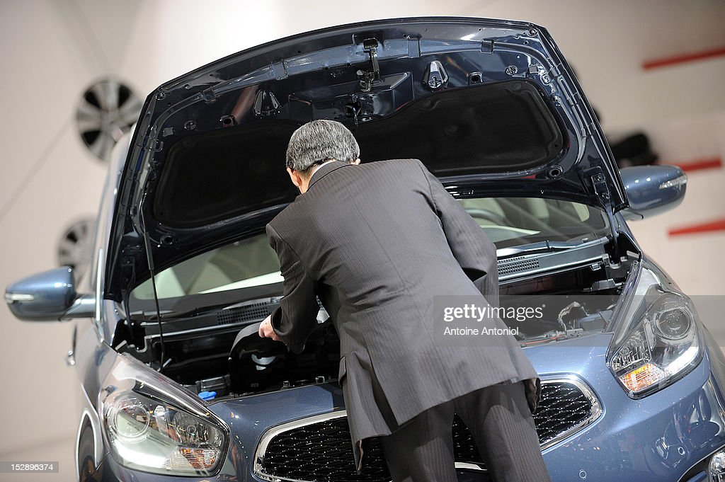 A visitor inspects the engine of a Kia Carens car at the Paris Motor Show on September 28, 2012 in Paris, France. The Paris Motor Show runs September 29 - October 14.