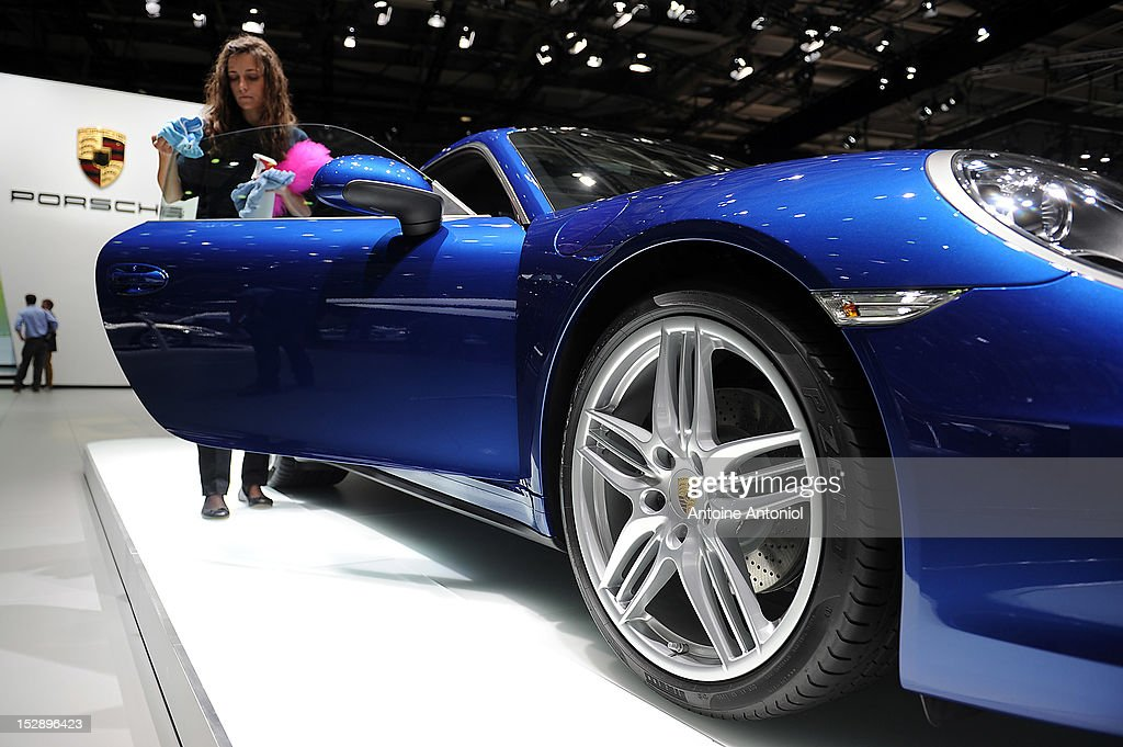 An employee cleans a Porsche Carrera 911 car at the Paris Motor Show on September 28, 2012 in Paris, France. The Paris Motor Show runs September 29 - October 14. The Paris Motor Show runs September 29 - October 14.
