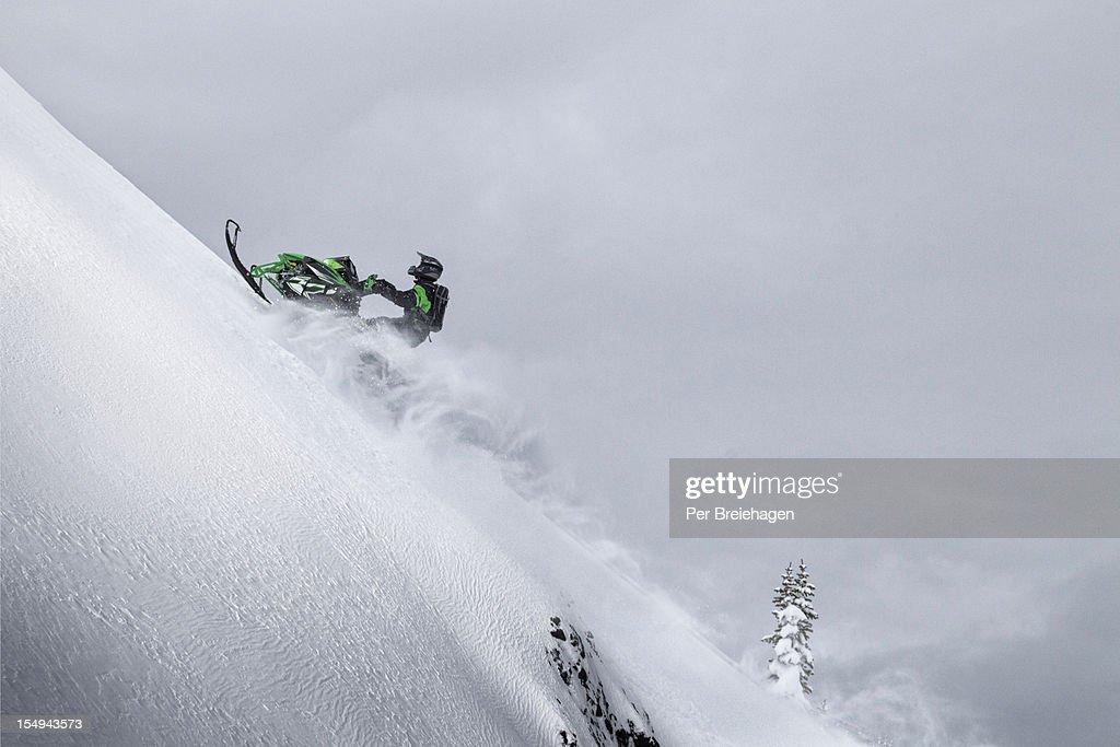 CLIMBING A STEEP MOUNTAIN ON A SNOWMOBILE : Stock Photo