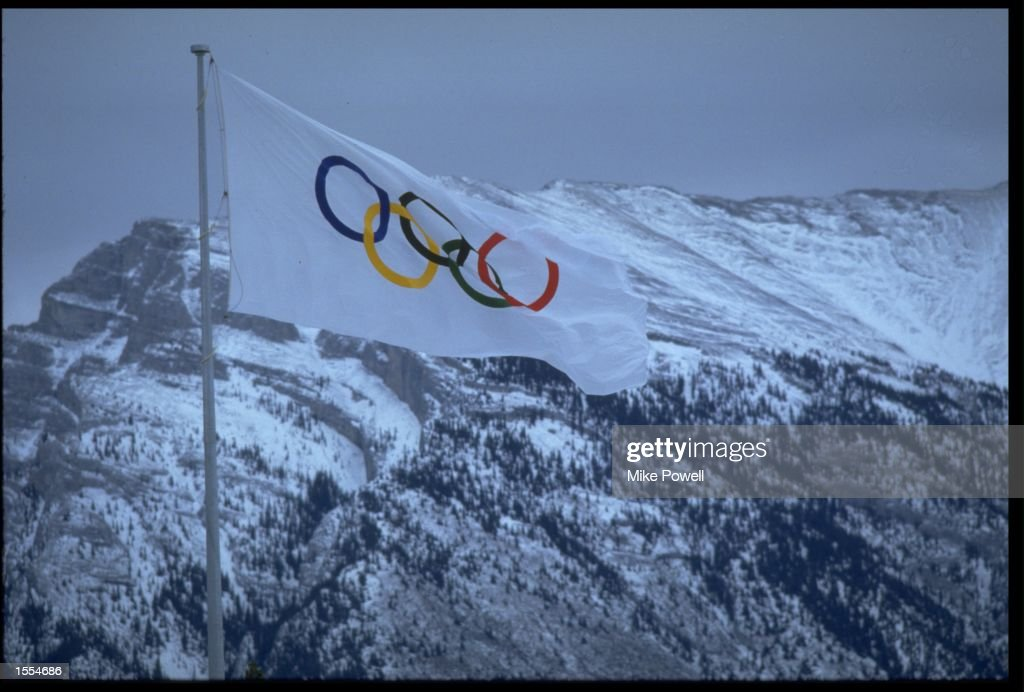 THE OLYMPIC FLAG BLOWS IN THE STRONG WINDS OF CANADA IN FRONT OF AN IMPRESSIVE BACKDROP OF SNOWY MOUNTAIN TOPS DURING THE 1988 WINTER OLYMPICS HELD IN CALGARY.