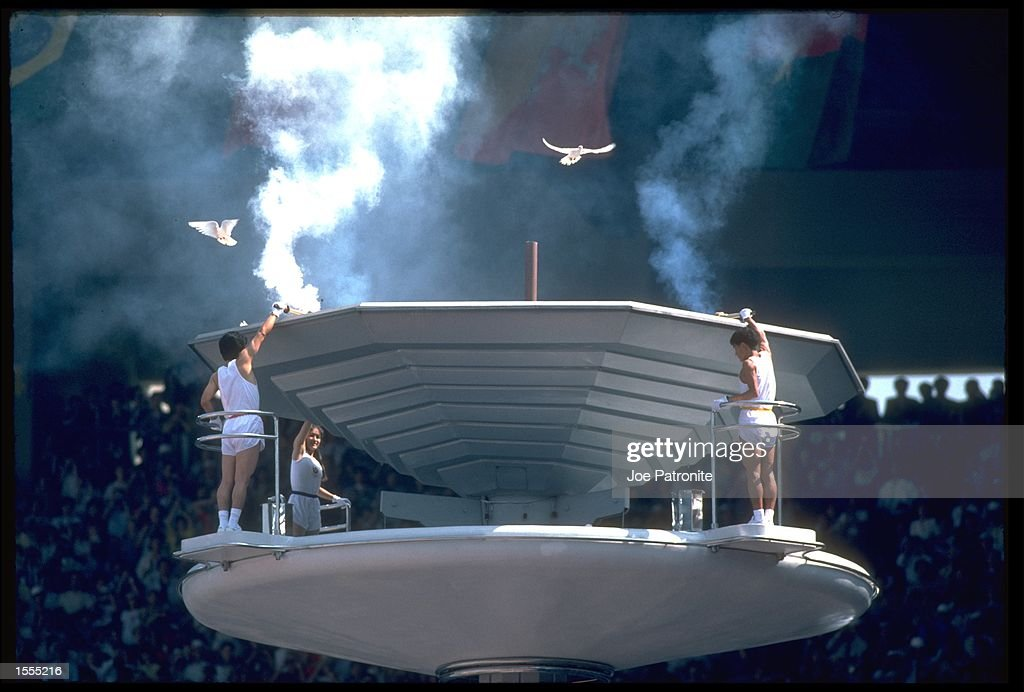 TORCH BEARERS PREPARE TO LIGHT THE OLYMPIC FLAME AS DOVES FLY THROUGH THE STADIUM DURING THE OPENING CEREMONY OF THE 1988 SEOUL OLYMPICS
