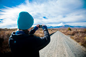 GIRL TAKES PICTURE OF MOUNTAINS IN NEW ZEALAND