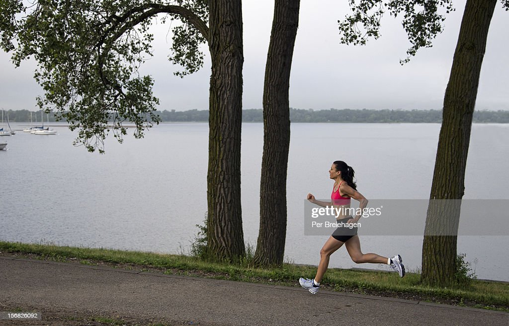 A FIT WOMAN RUNNING BY A LAKE : Stock Photo