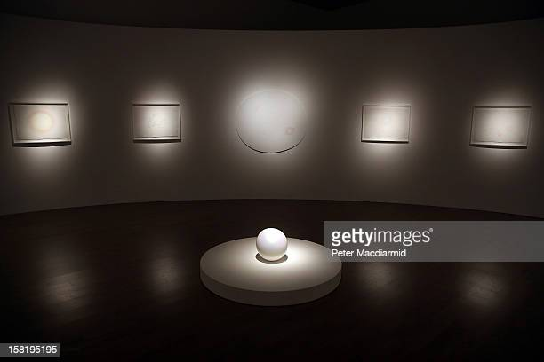 Various mixed media paintings are displayed with a spherical sculpture entitled 'Tama I' at the Mariko Mori Rebirth exhibition at The Royal Academy...