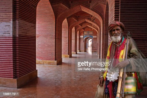 A BEGGAR IS STANDING AROUND THE ARCHES : Stock Photo
