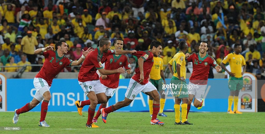 Morocco's Abdelilah Hafidi (foreground R) is congratulated by teammates after scoring a goal during the 2013 African Cup of Nations football match in Durban on January 27, 2013 in Durban at Moses Mabhida Stadium for a Group A match. The African Cup of Nations is been held in South Africa from January 19 - February 10.