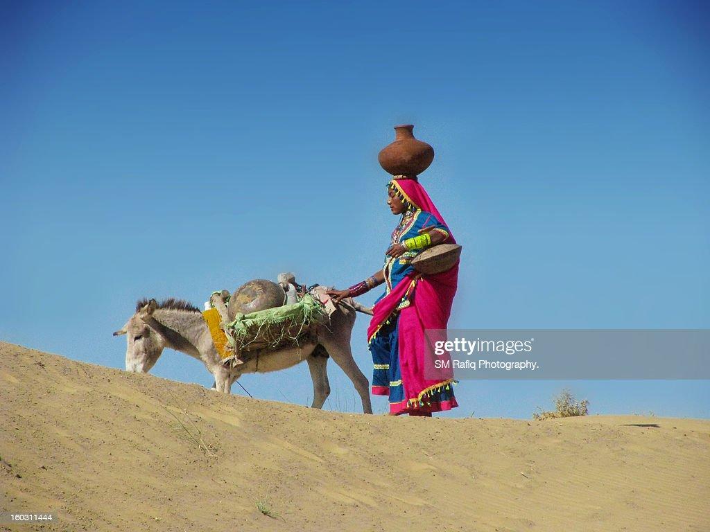 WOMEN CARRYING AWAY WATER IN DESERT : Stock Photo