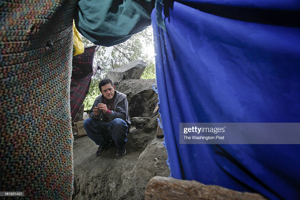 A man originally from the state of Sinaloa waits for a friend to return to their makeshift refuge in a canyon overlooking the fence that separates Mexico from the United States. The 44-year-old man, who declined to give his name, has lived in the United States for over a decade and was deported in early November of 2012 after his place of employment was raided by immigration officers. He was deported to the state of Tamaulipas. He has tried to return to his home and family in East Los Angeles 14 times since late November but has been caught by the border patrol. He now lives in this makeshift tent and hopes to return to his family in the near future. He works as a day laborer and a carpenter in the city of Tecate whenever he is able to find work. He used to be a carpenter in Los Angeles...Tecate, Baja California, Mexico - February 8, 2013. (Javier Manzano / For The Washington Post via Getty Images).