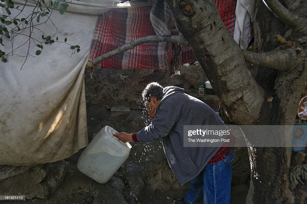 A man originally from the state of Sinaloa washes his face in a makeshift refuge in a canyon overlooking the fence that separates Mexico from the United States. The 44-year-old man, who declined to give his name, has lived in the United States for over a decade and was deported in early November of 2012 after his place of employment was raided by immigration officers. He was deported to the state of Tamaulipas. He has tried to return to his home and family in East Los Angeles 14 times since late November but has been caught by the border patrol. He now lives in this makeshift tent and hopes to return to his family in the near future. He works as a day laborer and a carpenter in the city of Tecate whenever he is able to find work. He used to be a carpenter in Los Angeles...Tecate, Baja California, Mexico - February 8, 2013. (Javier Manzano / For The Washington Post via Getty Images).