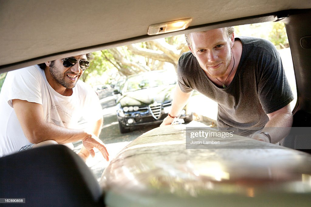 GUYS LOAD SURFBOARD IN TO BACK OF CAR : Stock Photo