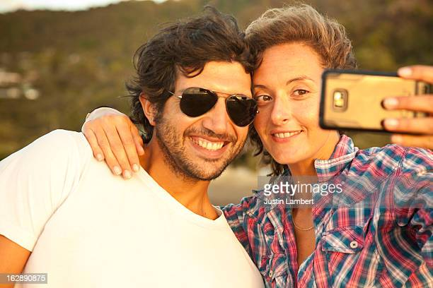 COUPLE TAKING A SELF-PORTRAIT INTO THE SUNLIGHT