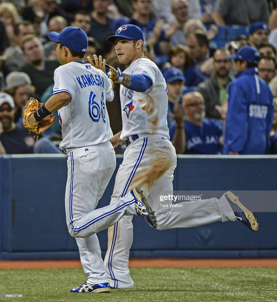 TORONTO, ON - Toronto Blue Jays' Brett Lawrie and Munenori Kawasaki high five on their way back to the dug out after wrapping up the third inning against the San Francisco Giants Wednesday MAY 15 in Toronto. - May 15, 2013.