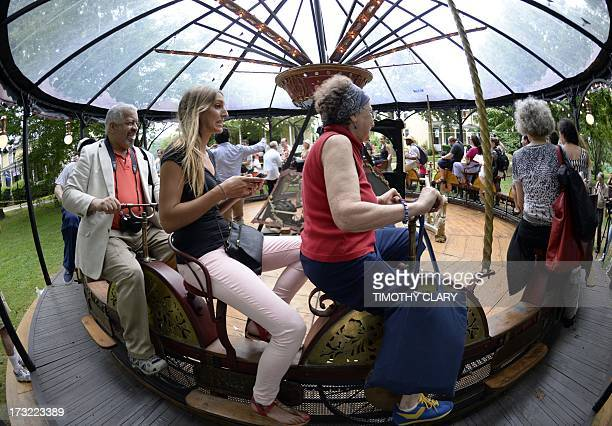 Members of the media and guest try out a ride during a press tour of Fête Paradiso the world's first festival of vintage French carnival rides and...