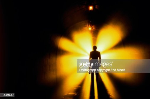SILHOUETTE OF MAN IN TUNNEL WITH LIGHTS