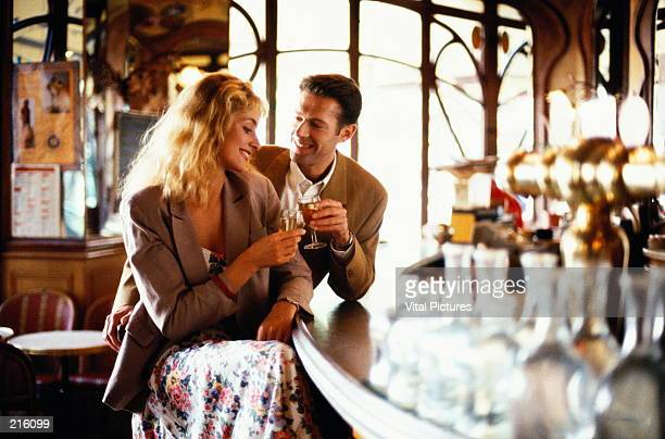 COUPLE WITH WINE AT BAR IN CAFE IN PARIS