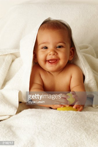 PORTRAIT OF SMILING BABY DRAPED WITH BLANKET : Stock Photo