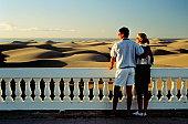 COUPLE VIEWING SAND DUNES & OCEAN IN SPAIN