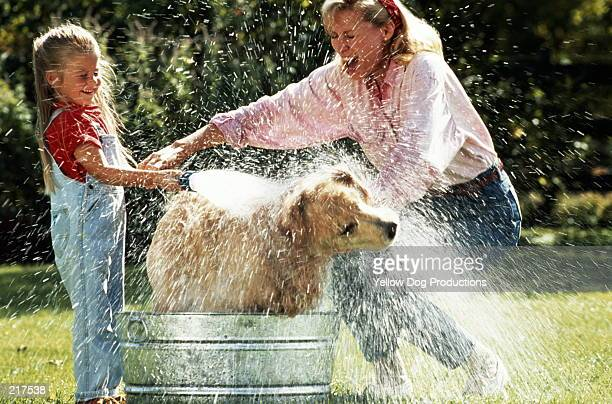MOTHER & DAUGHTER BATHING DOG