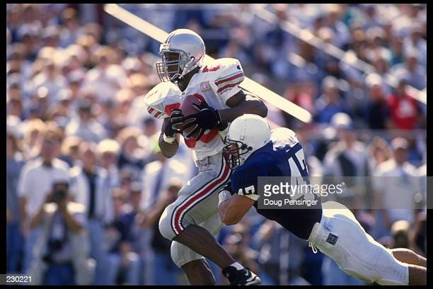OHIO STATE WIDE RECEIVER RICKEY DUDLEY IS TRIPPED UP BY PENN STATE LINEBACKER GERALD FILARDI DURING OHIO STATE''S 2825 WIN AT BEAVER STADIUM IN...