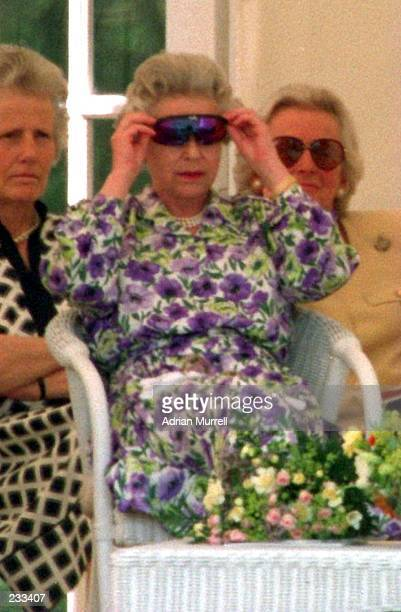 QUEEN ELIZABETH OF GREAT BRITAIN AND NORTHERN IRELAND TRIES ON THE SPECIALLY DESIGNED SUNGLASSES USED BY THE EXENGLAND CRICKET CAPTAIN DAVID GOWER...