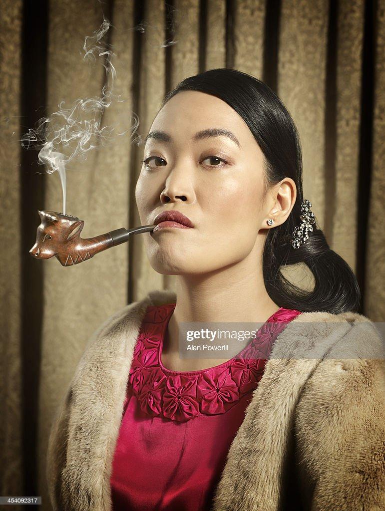 PORTRAIT OF WOMAN SMOKING PIPE