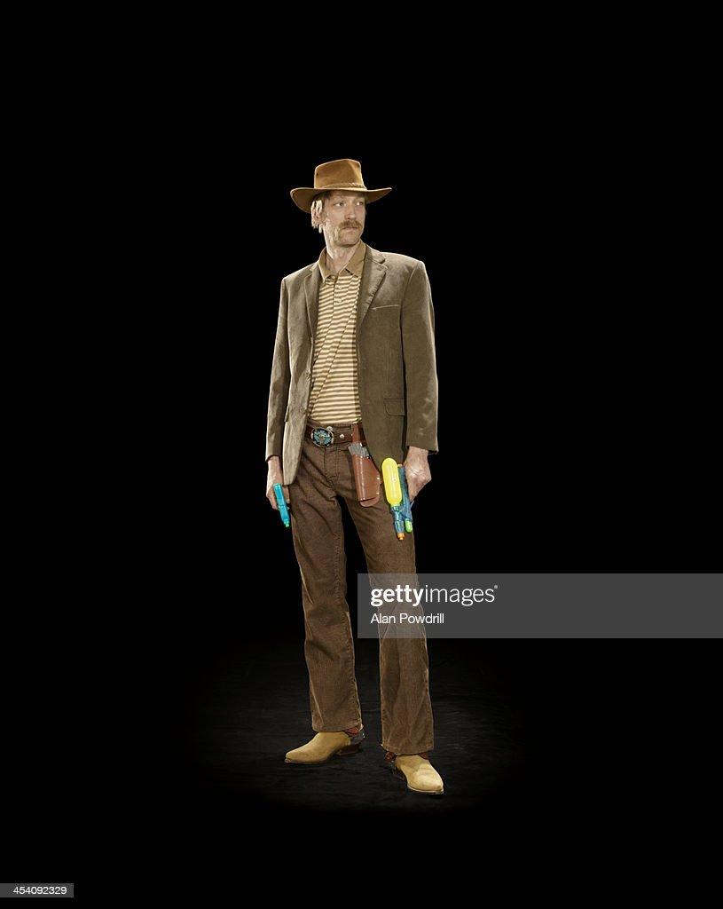 MAN DRESSED AS COWBOY WITH PLASTIC GUN