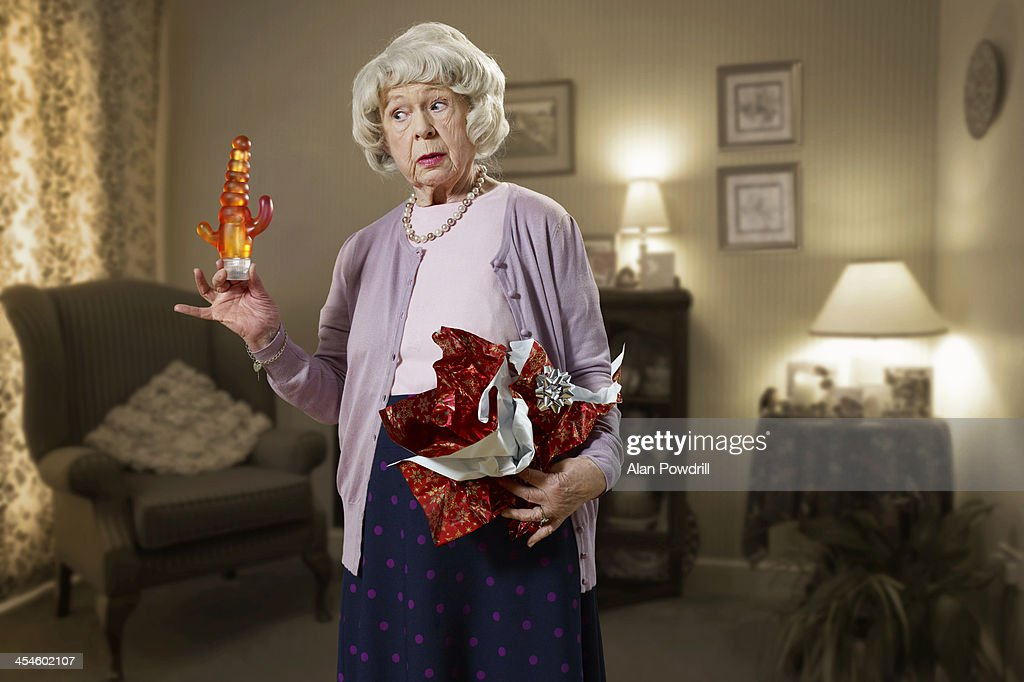 OLD WOMAN HOLDING A DILDO GIFT : Stock Photo