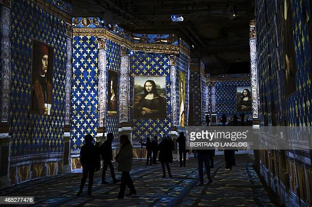 Visitors attend a preview of a sound and light show as part of the exhibition 'Michelangelo Leonardo da Vinci Raphael Giants of the Renaissance'...