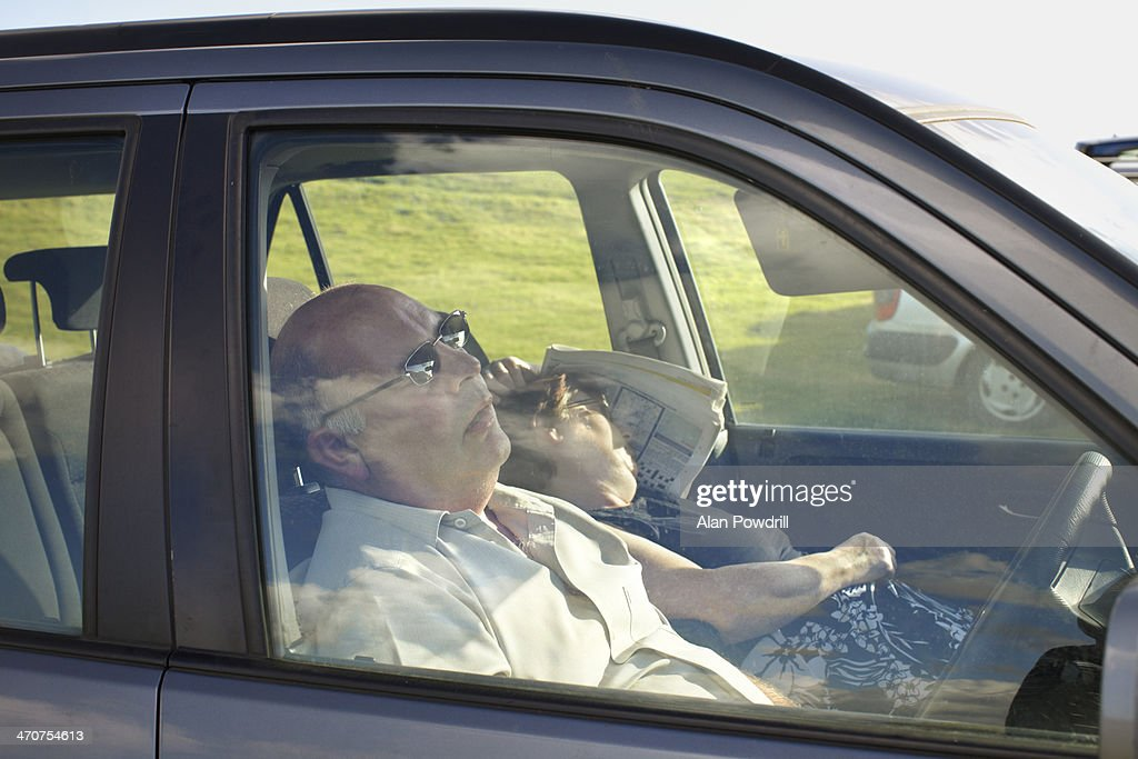 ELDERLY COUPLE ASLEEP IN THEIR CAR : Stock Photo