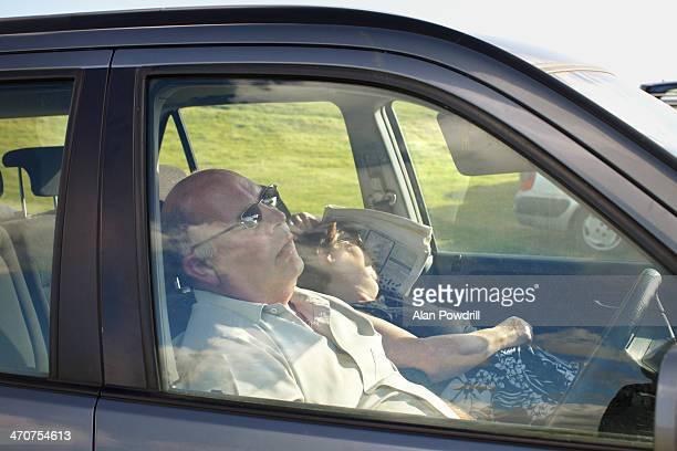 ELDERLY COUPLE ASLEEP IN THEIR CAR