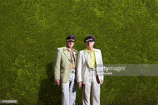 TWO ELDERLY MEN DRESSED IN 70'S OUTFITS