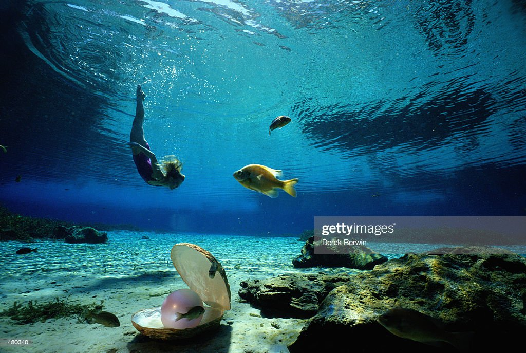 WOMAN SWIMMING UNDERWATER WITH PEARL : Stock Photo