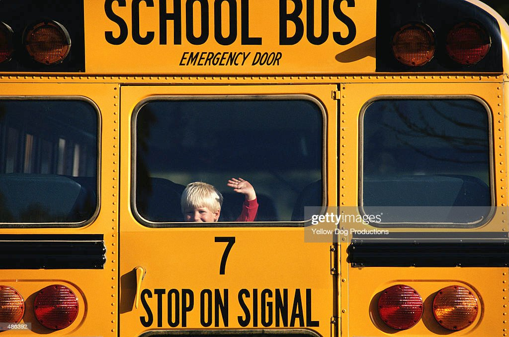 YOUNG BOY WAVING FROM BACK OF SCHOOL BUS : Stock Photo