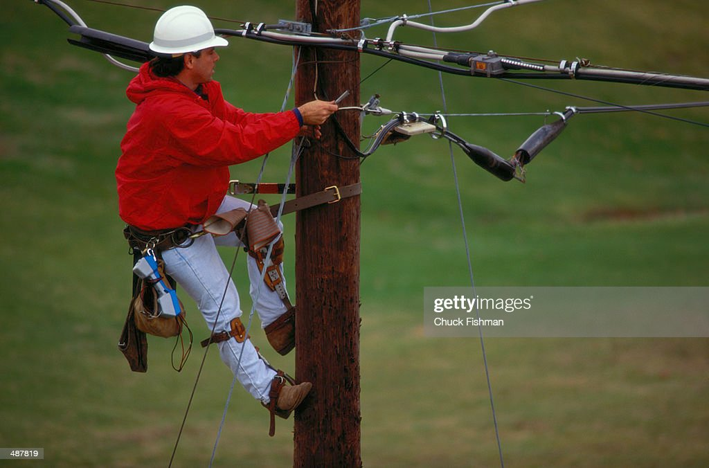 TELEPHONE REPAIRMAN ON POLE CHECKING LINE : Stock Photo